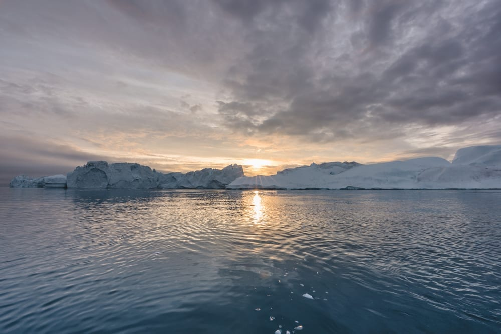 Arctic nature landscape with icebergs in Greenland icefjord with midnight sun sunset sunrise in the horizon. Early morning summer alpenglow during midnight season. Ilulissat, West Greenland. showing effects of climate change